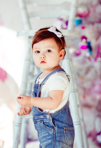 Busy little girl in jeans jumpers stands before tall white chair Free Photo