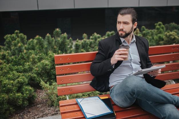 Занятый мужчина спешит, у него нет времени, он собирается перекусить на свежем воздухе. бизнесмен делает несколько задач. многозадачность делового человека. Premium Фотографии