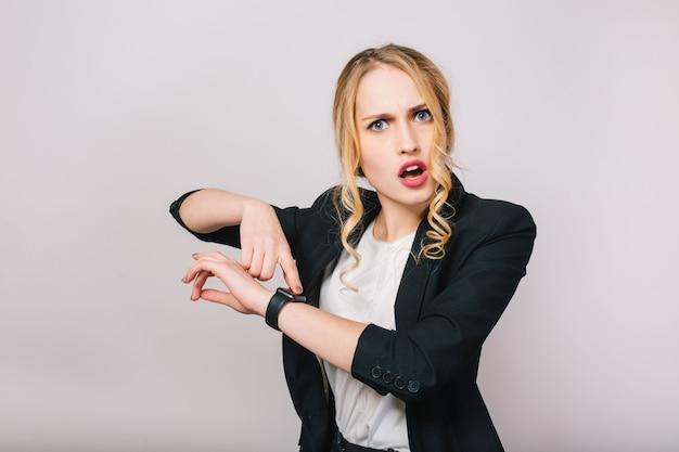 Tempo di lavoro d'ufficio occupato di giovane donna bionda stupita in camicia bianca e giacca nera che sembra isolata. incontrarsi, guardare, arrivare in ritardo, lavoratore, lavoro, manager Foto Gratuite