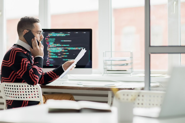 Busy programmer talking to customer by phone Premium Photo