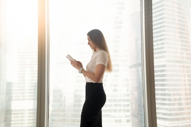 Busy serious businesswoman using digital tablet, standing near big window Free Photo