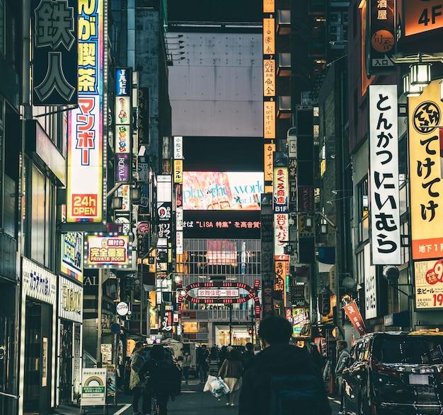 Оживленная улица в ночном городе с людьми и знаками Бесплатные Фотографии