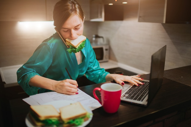 Busy woman eating, drinking coffee, talking on the phone, working on a laptop at the same time. businesswoman doing multiple tasks. multitasking business person. freelancer works at night. Premium Photo