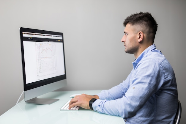바쁜 근무일. 젊은 수염 상인 노트북으로 작업하는 동안 차트 거래와 컴퓨터 화면 앞에 그의 현대적인 사무실에 앉아. 프리미엄 사진