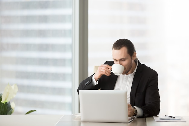 Busy young businessman drinks coffee Free Photo
