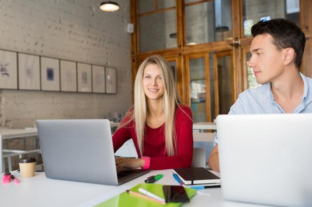 Giovane occupato e donna che lavorano al computer portatile nella stanza dell'ufficio di co-working dello spazio aperto Foto Gratuite