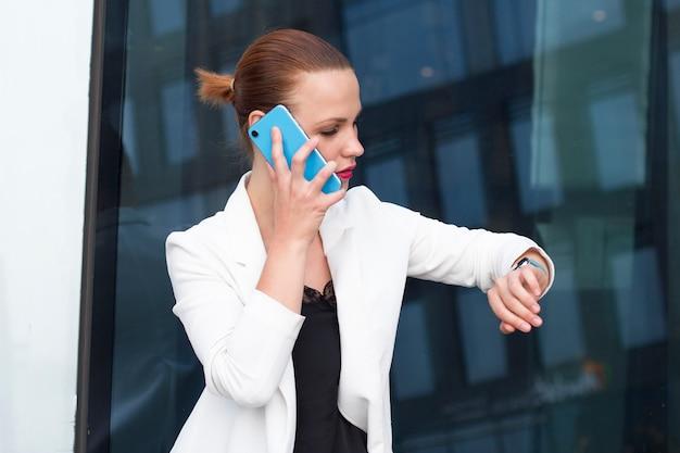 Занятая молодая успешная коммерсантка говоря на сотовом телефоне и смотря ее наручные умные часы. уверенно офис женщина вызова на смартфоне и контрольное время на smartwatch. Premium Фотографии