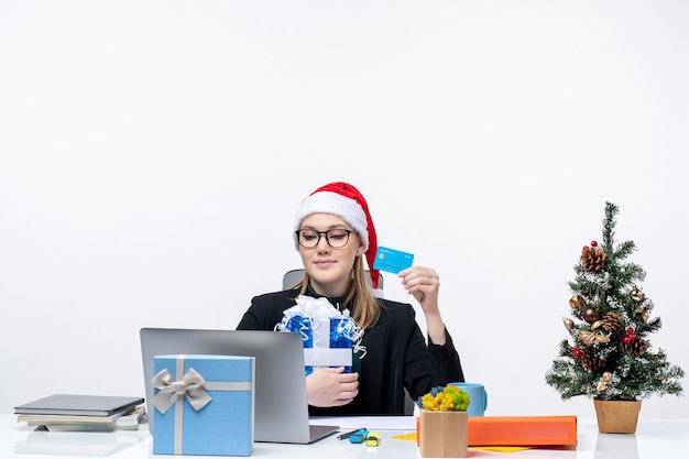 Busy young woman with santa claus hat and wearing eyeglasses sitting at a table holding christmas gift and bank card on white background Free Photo