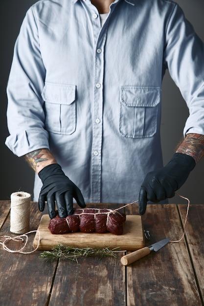 Мясник связывает мясо веревкой, чтобы коптить, на столе с видами Бесплатные Фотографии