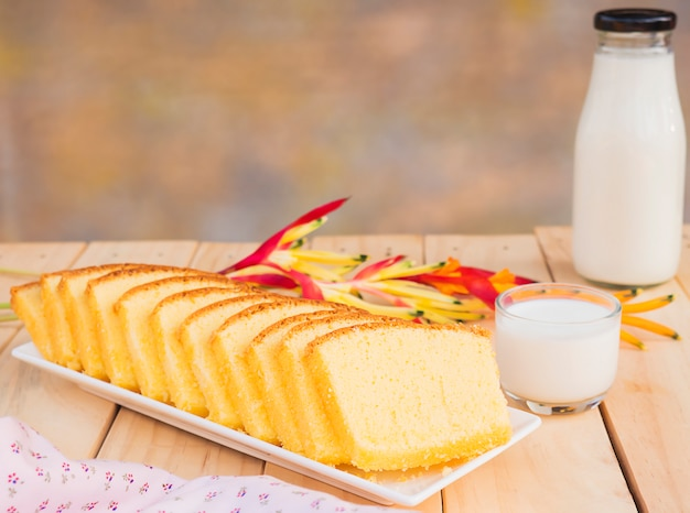 Butter cake and bottle with glass of milk on white wooden table Free Photo