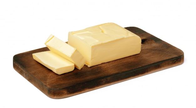 白い壁に分離された木の板にバター Premium写真