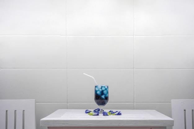 屋外フィールドのセメントの壁の前にパステルピンクの木製テーブルに蝶エンドウ豆。 Premium写真