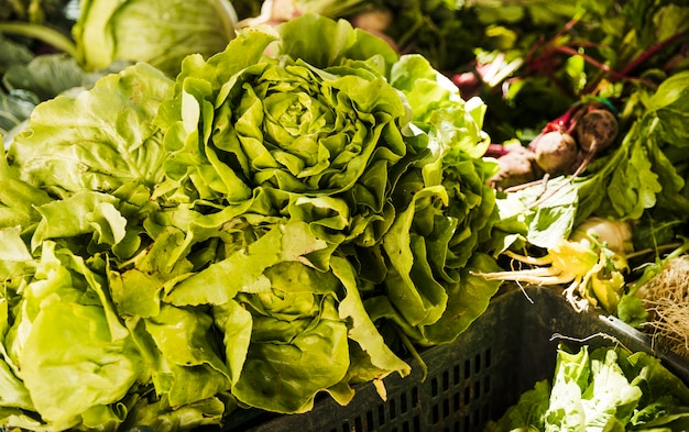 Butterhead lettuce with green vegetables on market stall at organic farmers grocery store Free Photo