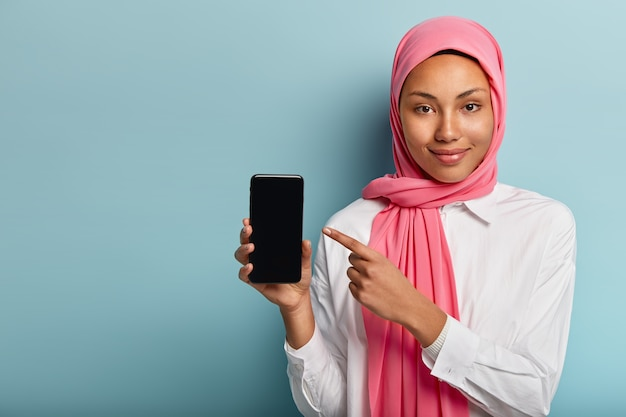 Buy this device! pleased dark skinned woman in pink veil, points at smart phone Free Photo