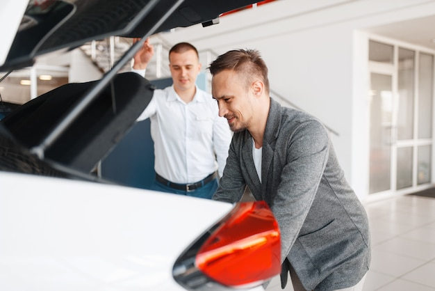 Buyer and manager looks at the trunk of new car in showroom. male customer choosing vehicle in dealership, automobile sale, auto purchase Premium Photo