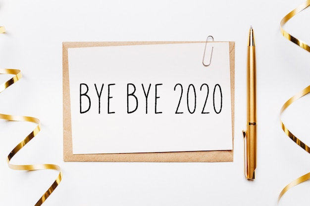 Premium Photo | Bye bye 2020 note with envelope, pen, gifts and gold ribbon  on white.