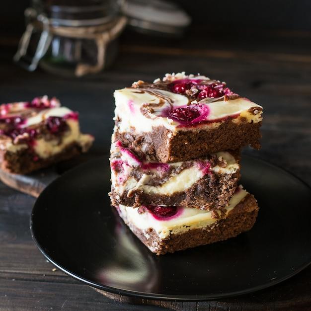 チョコレートチーズケーキは、ブラウニーとチェリーと一緒になっています。チョコレートチェリーケーキ。チョコレートc Premium写真