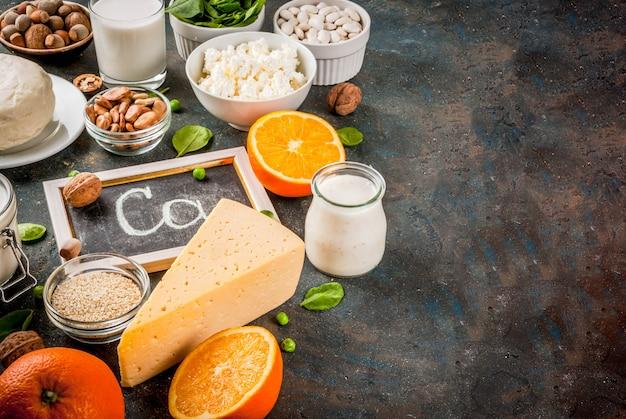 健康食品のコンセプト。カルシウムが豊富な食品のセット-乳製品とビーガンのca製品暗い青色の背景 Premium写真