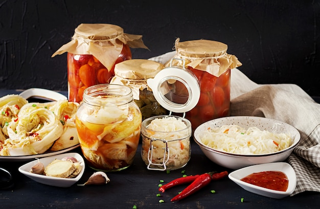 Cabbage kimchi, tomatoes marinated, sauerkraut sour glass jars over rustic kitchen table. Free Photo