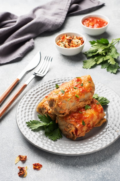 Cabbage rolls with beef, rice and vegetables on the plate. stuffed cabbage leaves with meat. gray concrete table Premium Photo