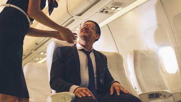 Personel pokładowy podaje wodę pasażerom w samolocie Premium Zdjęcia