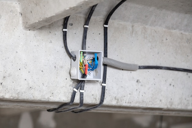 Cable laying ceiling. electrical wires on wall. concept wiring replacement, connecting light in flat or office, professional installation, electrical cables, wire, insulation Premium Photo