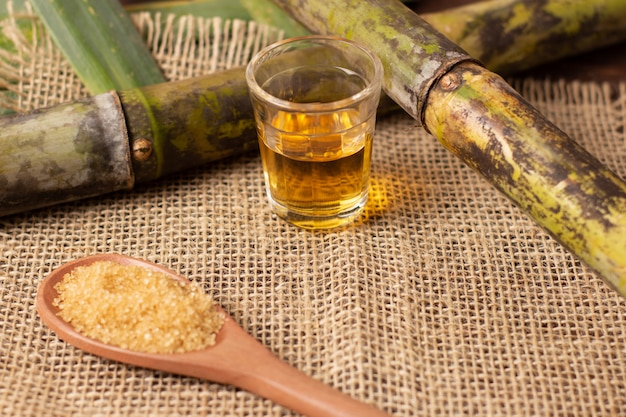 Cachaca is the name of a typical alcoholic drink produced in brazil maked with sugarcane. traditional drink from brazil on wooden table Premium Photo