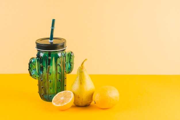 Cactus shape jar with pears and lemons on yellow background Free Photo