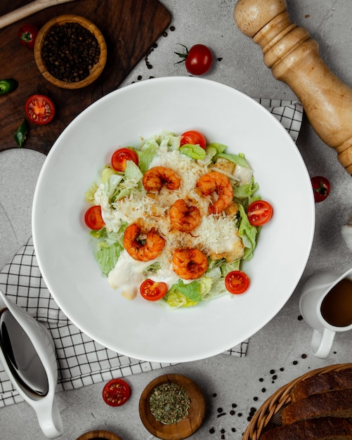 Caesar salad topped with fried shrimps Free Photo