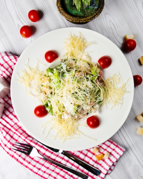 Caesar salad with cherry tomatoes and chopped parmesan. Free Photo