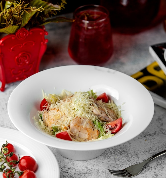 Caesar salad with chicken lettuce tomato and parmesan grates Free Photo
