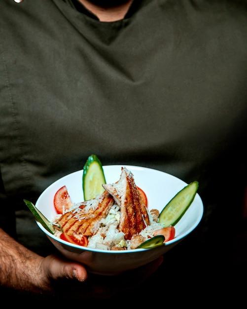Caesar salad with chicken in man hands Free Photo