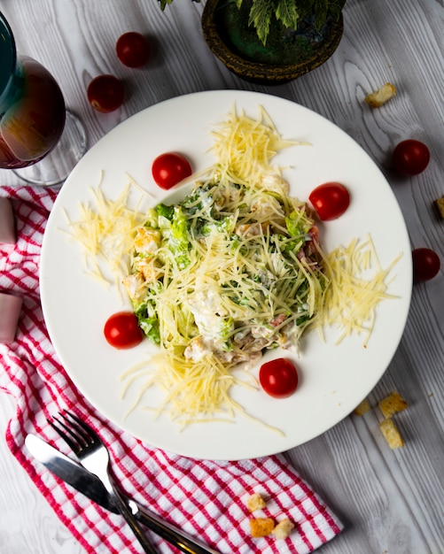 Caesar salad with chopped parmesan and cherry tomatoes, top view. Free Photo