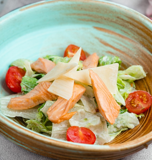 Caesar salad with fish fillet,  lettuce,  chopped parmesan slices and tomatoes. Free Photo