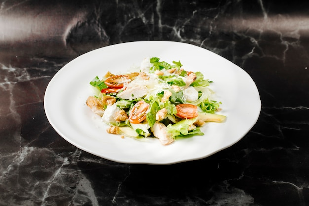 Caesar salad with mixed ingredienst inside white plate on a black marble. Free Photo