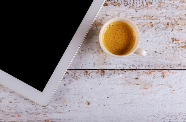 In cafe drinking coffee cup and digital tablet on old vintage table Premium Photo