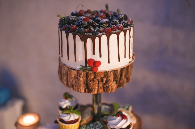 Cake and cupcakes with berries on a wooden shelf in candle light Premium Photo