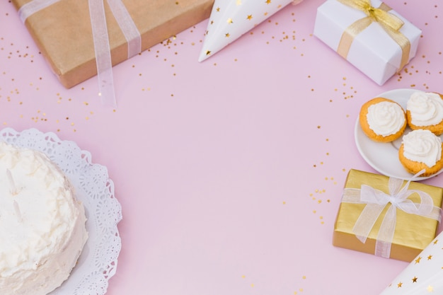 Cake; gift box; presents; gift box and confetti on pink backdrop Free Photo