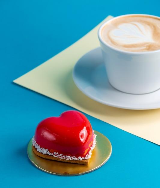 Torta mousse a forma di cuore torta su blu con una tazza di caffè Foto Gratuite
