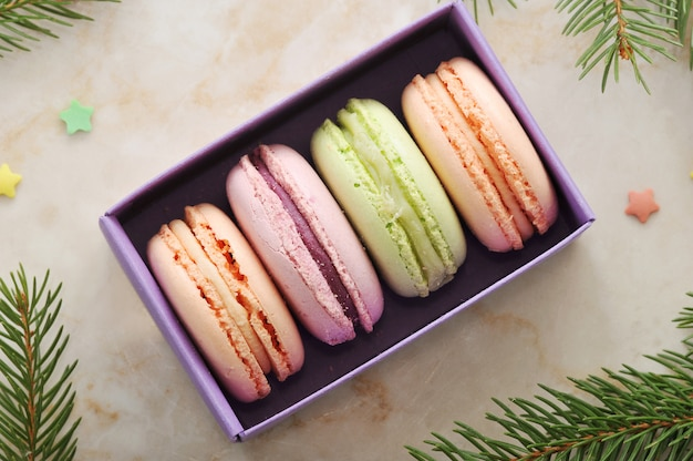 Cake macarons in a purple box with the branches of a christmas tree Premium Photo