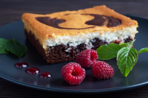 チョコレートブラウニーと豆腐チーズケーキのプレートにラズベリーを添えたケーキ。 Premium写真