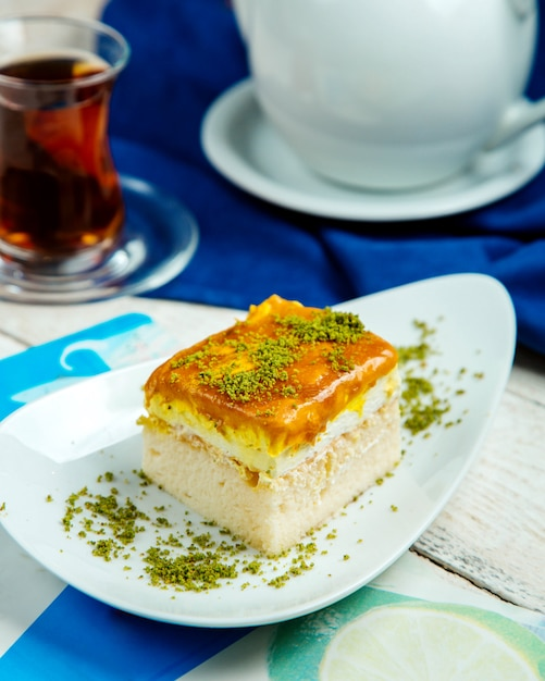 Cake piece with cream topped with caramel syrup and pistachio Free Photo