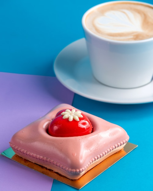 Torta mousse rosa torta con una tazza di caffè su blu e viola Foto Gratuite