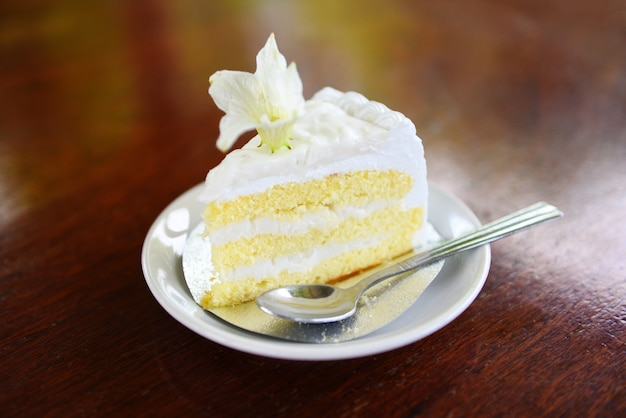 Cake slice on white palte with flower on wooden table background coconut cake Premium Photo