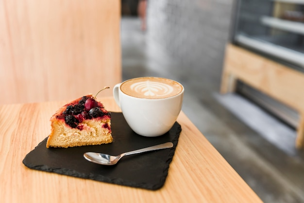 Cake slice with spoon and cappuccino coffee on shale board over the wooden table Free Photo