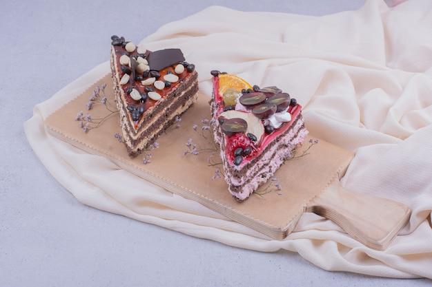木製の大皿にキャラメル、チョコレート、ナッツのケーキスライス。 無料写真