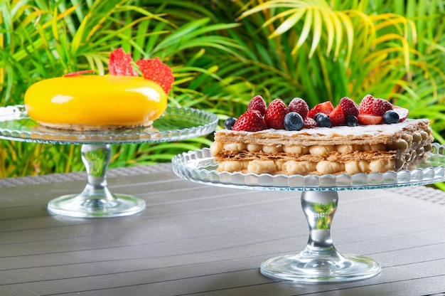 Cake stands with creative desserts against tropical background Free Photo