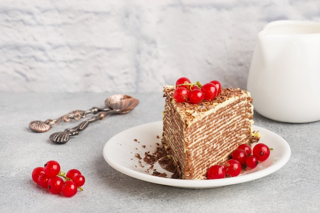 Cake of thin chocolate pancakes and pistachio cream with red currant berries Premium Photo