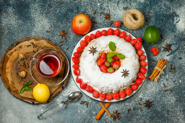 フルーツ、ストレーナー、お茶、糸、スパイス、砂糖、木の板と漆喰背景、上面のプレートにハーブとケーキ。 無料写真