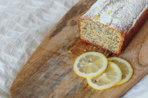 Cake with poppy seeds and lemon zest, sprinkled with powdered sugar. cupcake with lemon on a wooden board. Premium Photo